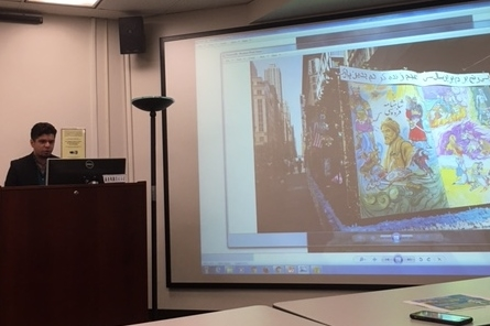 Arsia Rozegar presents with one of his illustration's of the Shahnameh in the background